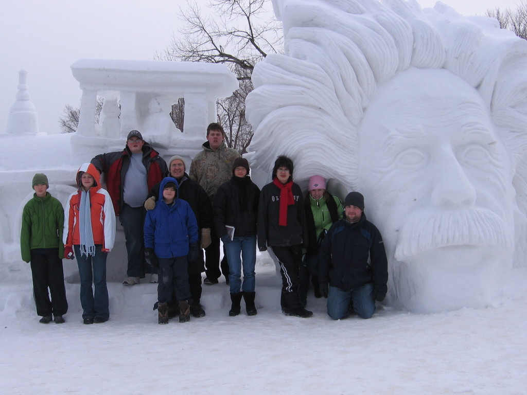 7 students and two adults standing in front of  snow sculpture