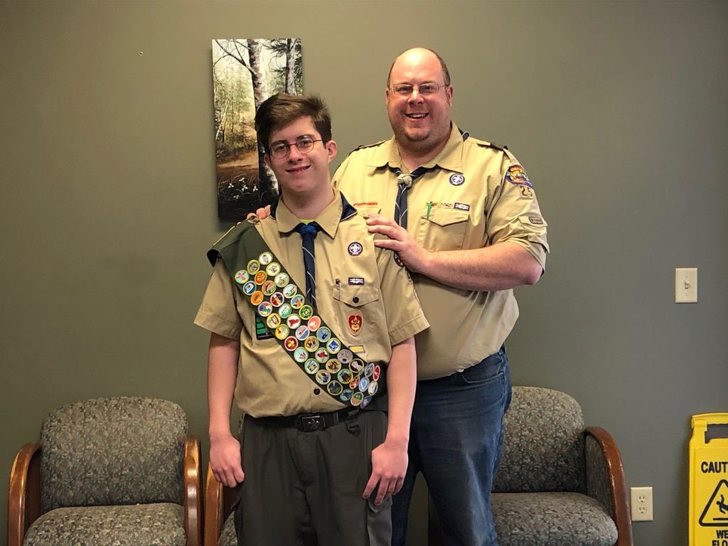Image of Student Bryce Bernard with his father, wearing a brown boy scout shirt and a sash with badges.