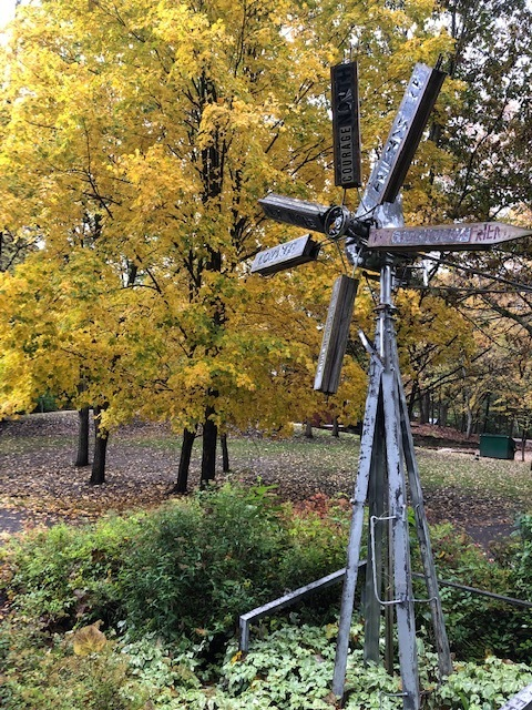 Windmill in front of trees with yellow leaves