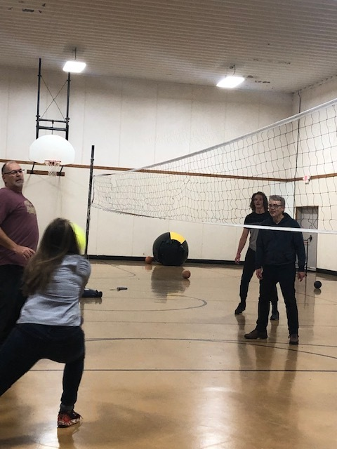 Advisor bups a ball while other advisors look on at a volleyball game