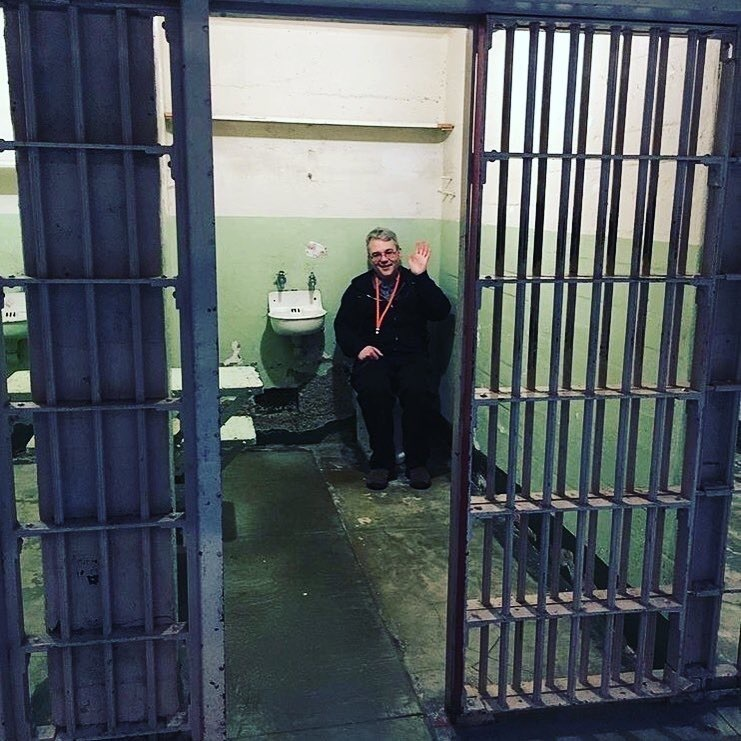Advisor Larry in a jail cell on a field trip.