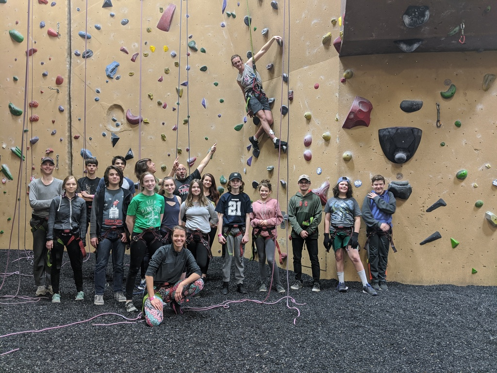 Group of students in front of rock climbing wall