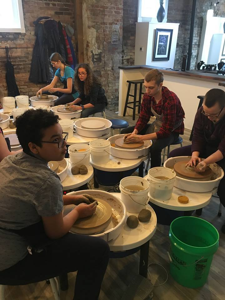 Students using pottery wheels to create art
